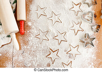 Heart and star shaped cookie cutters made by professional unknown cook, rolling pins for making thin dough. Home made Christmas cookies ready to be baked. Gingerbread made of different forms.