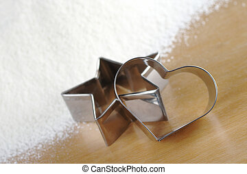 Heart and star shaped cookie cutters with flour in the...