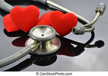 Heart and stethoscope on dark background.