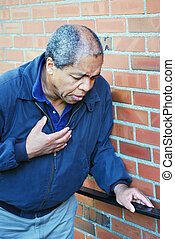 Heart attack victim. - African american male having a heart...