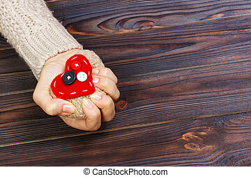 Heart Attack with both Hands on wooden background. Love concept with copyspace