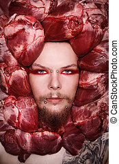 Conceptual close-up portrait of pierced and tattooed man with raw bloody hearts around his face