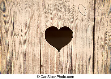 Heart carved in a wooden board. Background.