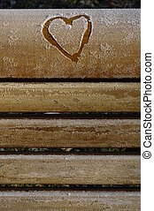 Heart drawn in the frost on a wooden bench