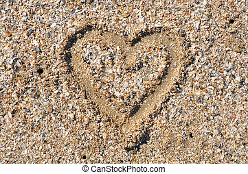 Heart drawn in the sand. Beach back