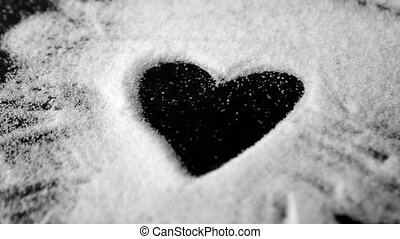 Heart drawn into sugar being blown out in slow motion