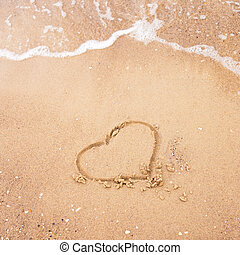 Heart drawn on a sand of beach with the wave of the sea. Free space for your text. Summer holiday concept. Romantic love background. Valentine's Day theme. Top view. Copy space.
