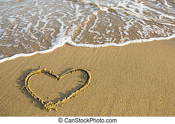 Heart drawn on the sand of a beach.