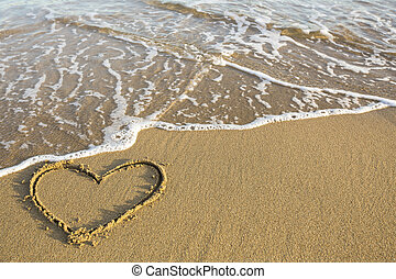Heart drawn on the sand of a sea beach.