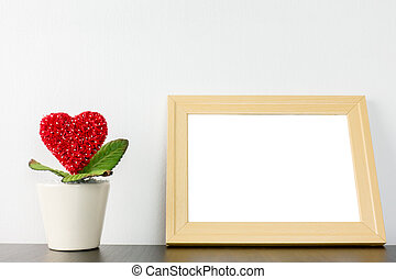 Heart flower in wihite pot with wooden photo frame