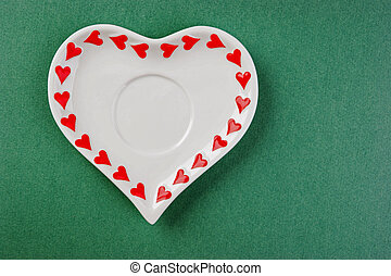 Heart form white plate on a green background