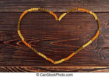 Heart frame from colorful fusilli pasta.
