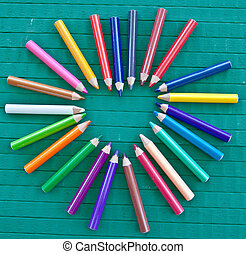 Heart frame made of colorful crayons on green wooden...