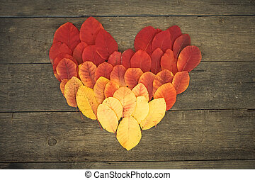Heart from autumn leaves on a wooden background