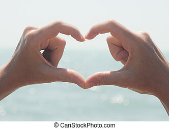 Heart from hands on sea-view