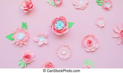 Heart from rose paper flowers on pink background. Cut from...