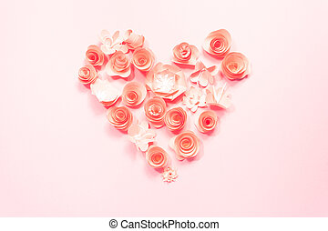Heart from rose paper flowers on pink.