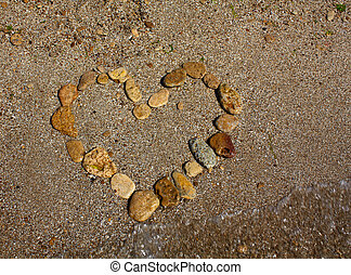 Heart from stones on sand seacoast