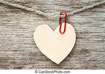 Heart  hanging on wooden background.