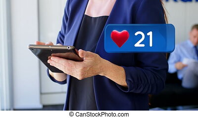 Heart icon and a woman using a digital tablet