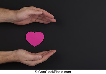 Heart in a palm on dark background with copy space