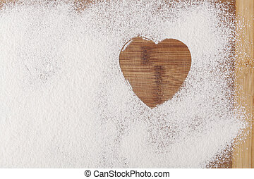 Heart in Flour - Heart shape flour on brown wood cutting...