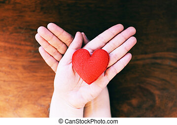 Heart in hand for philanthropy concept - woman holding red heart on hands for valentines day or donate help give love warmth take care with wooden background