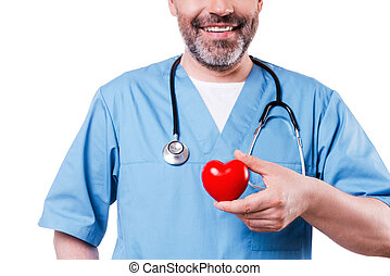 Heart in his hand. Close-up of mature cardiology surgeon holding heart shape toy and smiling while standing isolated on white