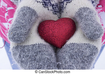 Heart in the girl's hands. Young woman holding heart mittens in winter