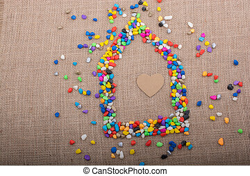 Heart in the house form shaped by pebbles