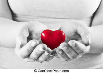 Heart in woman hands. Love giving, care, health, protection concept. Black and white