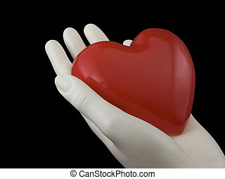 Photo of a hand holding a heart isolated on black