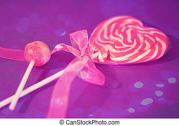 a pink heart lollipop with cute ribbon with bokeh overlay