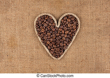 Heart made from rope with coffee beans lying on sackcloth
