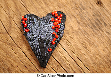 heart made of cloth with red beads on old wood with copy space, concept about love at Christmas, Mother's Day or Valentine's Day