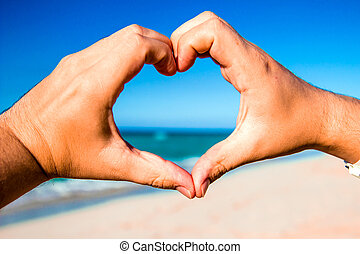 Heart made ??of hands at the beach with the ocean on...