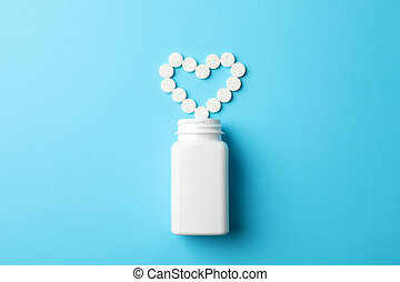 Heart made of pills and blank bottle on blue background, space for text