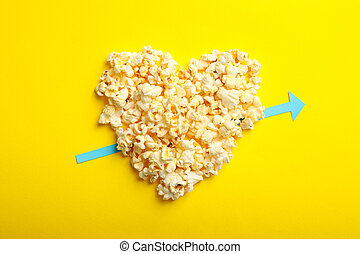 Heart made of popcorn on yellow background
