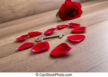 Heart made of red rose petals with a key lying in the middle