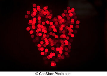 Heart made of shiny bokeh lights in red color