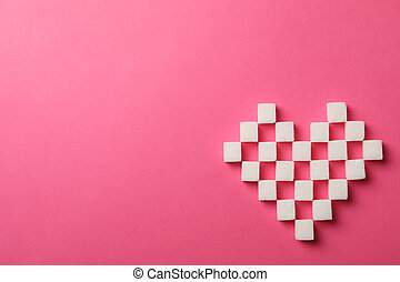 Heart made of sugar cubes on pink background, top view