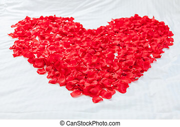 Heart made with flowers on honeymoon bed