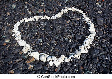 Heart made with white stone on black stone