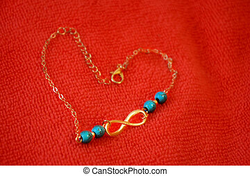 Heart of a gold chain on a microfiber cloth. The symbol of infinity with stones from turquoise. Endless love.