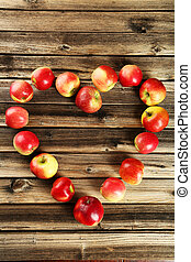Heart of apples on brown wooden background