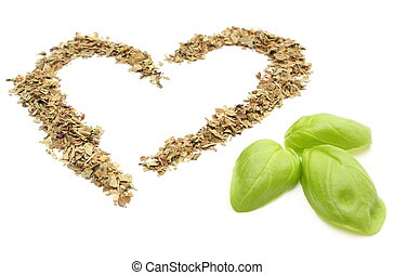 Heart of dried basil with green leaves on white background