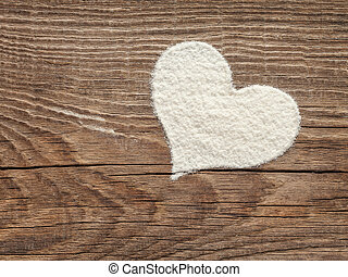 heart of flour on old wooden board