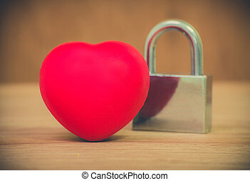 Heart of love and lock on wooden background