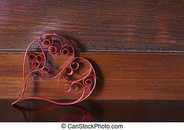 Heart of quilling paper on a wooden background