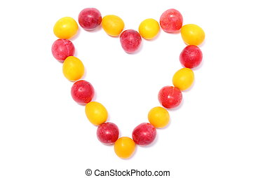 Heart of red and yellow mirabelle on white background